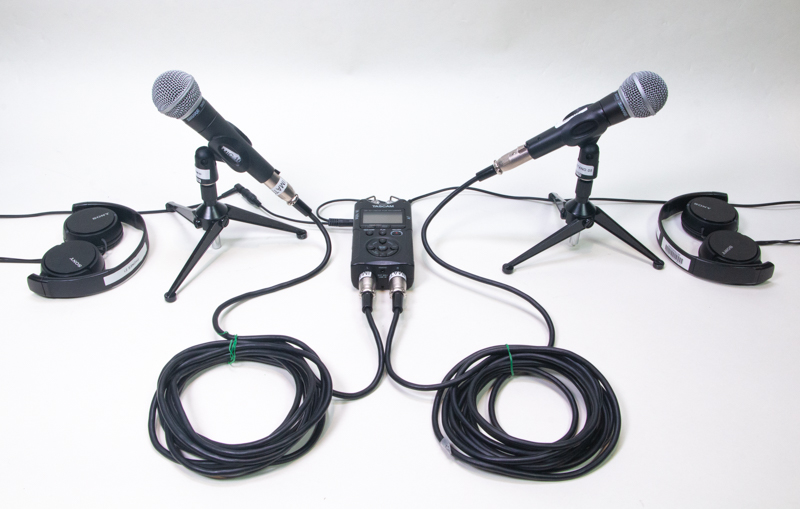 A pair of Shure microphones, a Tascam recorder, wires, and a pair of Sony headphones